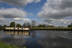 Travel boating Yorkshire. A barge with a male sailor on the South Yorkshire Canal system near Selby, with cloud reflections in the water Royalty Free Stock Images