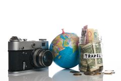 Travel budget concept, close-up. Travel budget concept. Travel money savings in a glass jar with photo camera and globe on a white background, close-up Royalty Free Stock Images
