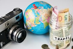 Travel budget concept, close-up. Travel budget concept. Travel money savings in a glass jar with photo camera and globe on a white background, close-up Stock Photos