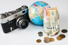 Travel budget concept, close-up. Travel budget concept. Travel money savings in a glass jar with photo camera and globe on a white background, close-up Royalty Free Stock Photography