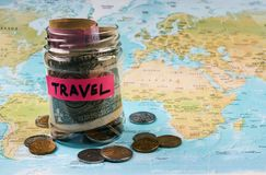 Travel budget concept, close-up. Vacation money savings in a glass jar with travel text . World map background. Travel budget concept, close-up Stock Image