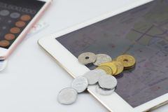 Travel budget concept. Coins on tablet and map. Background on white background Royalty Free Stock Photography