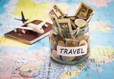 Travel budget concept with compass, passport and aircraft toy. Travel budget concept. Travel money savings in a glass jar with compass, passport and aircraft toy Stock Photo