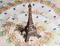 Travel budget concept. Eiffel Tower souvenir surrounded by vacation money. A lot of euro bills. Travel budget concept Stock Photos