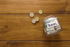 Travel budget concept. Money saved for vacation in glass jar on map. Travel budget concept. Money saved for vacation in glass jar on wooden background, copy Royalty Free Stock Photography