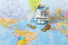 Travel budget concept. Money saved for vacation in glass jar on map. Travel budget concept. Money saved for vacation in glass jar on world map background, copy Stock Images