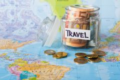 Travel budget concept. Money saved for vacation in glass jar on map. Travel budget concept. Money saved for vacation in glass jar on world map background, copy Royalty Free Stock Image