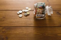 Travel budget concept. Money saved for vacation in glass jar on map. Travel budget concept. Money saved for vacation in glass jar on wooden background, copy Royalty Free Stock Photo