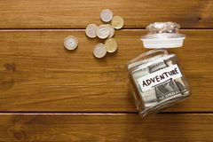 Travel budget concept. Money saved for vacation in glass jar on map. Travel budget concept. Money saved for vacation in glass jar on wooden background, copy Stock Photography