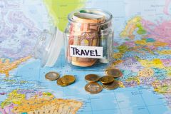 Travel budget concept. Money saved for vacation in glass jar on map. Travel budget concept. Money saved for vacation in glass jar on world map background, copy Stock Photos