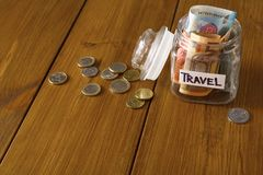 Travel budget concept. Money saved for vacation in glass jar on map. Travel budget concept. Money saved for vacation in glass jar on wooden background, copy Stock Image