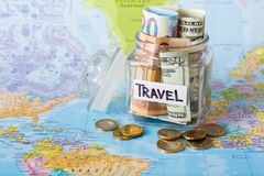 Travel budget concept. Money saved for vacation in glass jar on map. Travel budget concept. Money saved for vacation in glass jar on world map background, copy Royalty Free Stock Photography