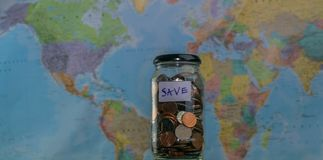 Travel budget concept. Money saved for vacation in glass jar on world map background, copy space. coins for big Royalty Free Stock Photography