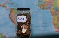 Travel budget concept. Money saved for vacation in glass jar on world map background, copy space. coins for big Stock Photography