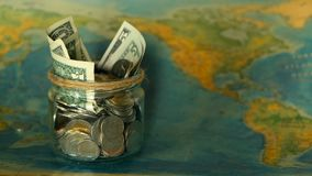 Travel budget concept. Money saved for vacation in glass jar on world map background. Copy space. Banknotes and coins for adventure. Savings for journey stock video footage