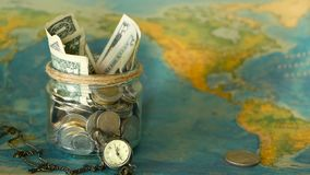 Travel budget concept. Money saved for vacation in glass jar on world map background. Copy space. Banknotes and coins for adventure. Savings for journey stock footage
