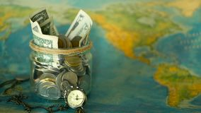 Travel budget concept. Money saved for vacation in glass jar on world map background. Copy space. Banknotes and coins for adventure. Savings for journey stock video
