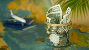 Travel budget concept. Money saved for vacation in glass jar on world map background. Travel budget concept. Money saved for vacation in glass jar with world map stock video footage