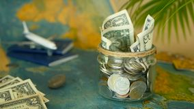 Travel budget concept. Money saved for vacation in glass jar on world map background. Travel budget concept. Money saved for vacation in glass jar with world map stock video
