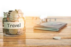 Travel budget concept. Travel money savings concept. Collecting money in the money jar for travel. Money jar with coins, aircraft. stock image
