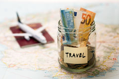 Travel budget concept, money savings in a glass jar. On a map Royalty Free Stock Image