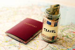 Travel budget concept, money savings and passport on a map Stock Photos