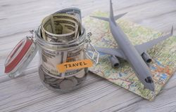 Travel budget concept. Travel money savings in a glass jar with aircraft toy. On world map Stock Images