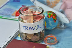 Travel budget concept. travel money savings in a glass jar with compass, passport and aircraft toy Royalty Free Stock Photography