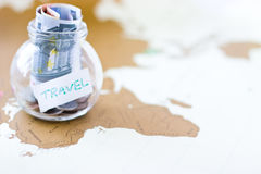 Travel budget - vacation money savings in a glass jar on world m Royalty Free Stock Photography