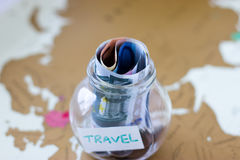 Travel budget - vacation money savings in a glass jar on world m Stock Photography