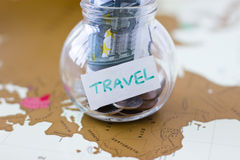 Travel budget - vacation money savings in a glass jar on world m Stock Photos