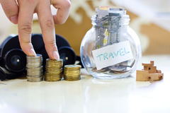 Travel budget - vacation money savings in a glass jar on world m Royalty Free Stock Images