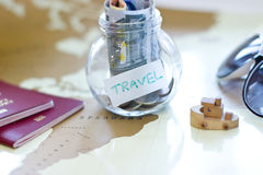 Travel budget - vacation money savings in a glass jar on world m Stock Images