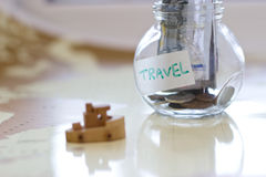 Travel budget - vacation money savings in a glass jar on world m Royalty Free Stock Photo