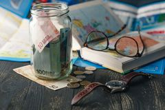 Travel budget - vacation money savings in a glass jar on world m Royalty Free Stock Photos