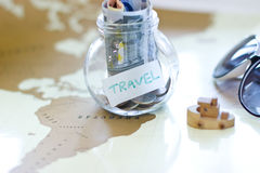 Travel budget - vacation money savings in a glass jar on world map. Royalty Free Stock Images