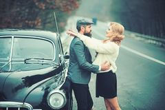 Travel and business trip or hitch hiking. Bearded man and sexy woman in fur coat. Retro collection car and auto repair. Travel and business trip or hitch hiking stock photography