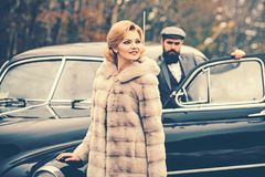 Travel and business trip or hitch hiking. Bearded man and sexy woman in fur coat. Retro collection car and auto repair royalty free stock images