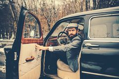 Travel and business trip or hitch hiking. Escort man or security guard. Call boy in vintage auto. Bearded man in car. Retro collection car and auto repair by royalty free stock photography