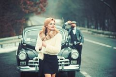 Travel and business trip or hitch hiking. Retro collection car and auto repair by mechanic driver. Escort of girl by. Security. Bearded men and sexy women in stock images