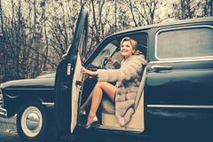 Travel and business trip or hitch hiking. sexy woman in fur coat. Escort and security guard for luxury woman. Call girl. In vintage car. Retro collection car royalty free stock photo