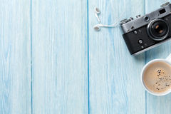 Travel camera and coffee cup on wooden table Stock Image