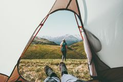 Travel camping couple view from tent entrance. Women walking in mountains men feet relaxing inside Lifestyle concept adventure summer vacations outdoor Stock Image