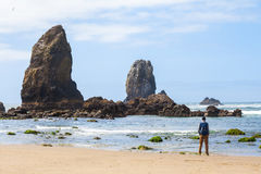 Travel in Canon Beach, man with backpack enjoying view ocean, on the beach, USA royalty free stock photos