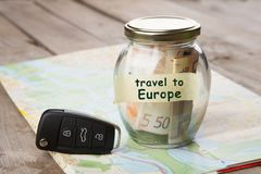 Travel by car to Europe - money jar, car key and roadmap. Rent auto rental sale security driving insure buy alarm vehicle service business open system insurance royalty free stock photography