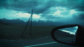 Travel by car. A view of the snowy mountains in the evening. Cloudy sky can be seen through the rearview mirror. Travel by car. A view of the snowy mountains in stock footage