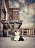Travel Child Waiting with Suitcase and Teddy Bear. A little child is sitting on a travel suitcase by an old building with teddy bear next to her for a strength Stock Photography