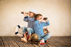 Travel. Children playing with vintage nautical things. Kids having fun at home. Travel and adventure concept. Retro toned image Stock Image