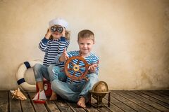 Travel. Children playing with vintage nautical things. Kids having fun at home. Travel and adventure concept. Retro toned image Stock Photography