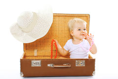 Travel, children, vacation - concept. Cute funny baby playing. In sunglasses and summer straw hat looks out of a suitcase Stock Photo